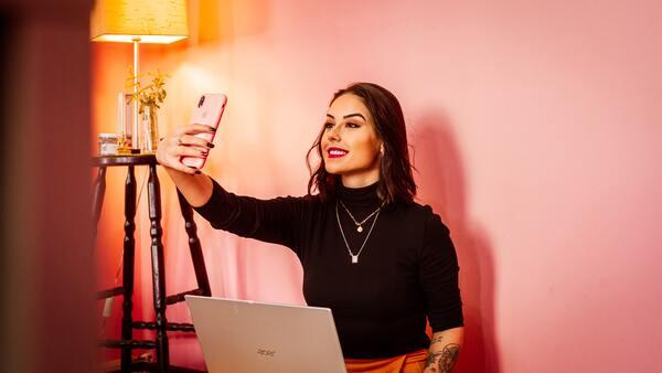 A imagem contém uma profissional influencer fazendo uma selfie com celular.