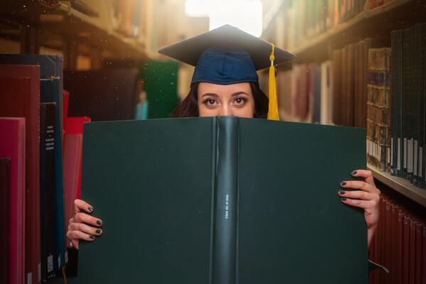 A imagem contém uma jovem segurando um grande livro. Ela se encontra atrás desse livro aberto e só é possível ver seus olhos. Sua expressão é de curiosidade quanto à sua vocação.