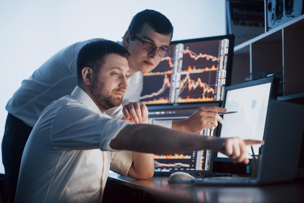 A imagem contém dois jovens. Um está sentado e apontando para a tela do computador, mostrando investimento para estudantes. O outro está de pé e olha para a tela para a qual seu colega está apontando.