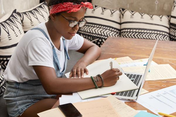 A imagem contém uma jovem estudante escrevendo em um papel e mostrando como é essencial saber como organizar os estudos na faculdade.