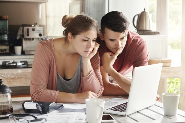 A imagem contém um casal debruçado sobre o notebook aberto, aprendendo sobre mercado financeiro para iniciantes.