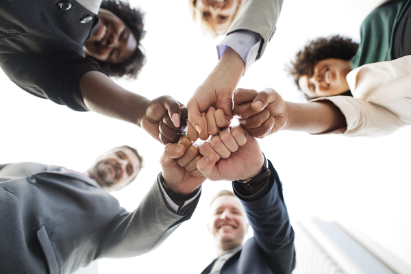 A imagem contém um grupo de jovens, sendo três mulheres e dois homens desenvolvendo suas soft skills na empresa ao trabalharem em equipe. Os jovens unem as mãos fechadas ao centro do círculo.