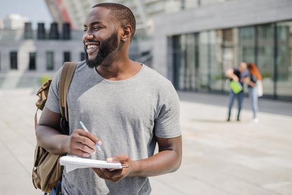 A imagem contém um sorridente jovem estudante de graduação em tecnologia.
