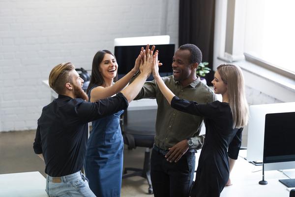 A imagem contém quatro jovens, sendo duas mulheres e dois homens com uma das mãos erguidas e juntas às dos outros. Isto é o que é intraempreendedorismo: saber tomar decisões em equipe como se fossem empreendedores.