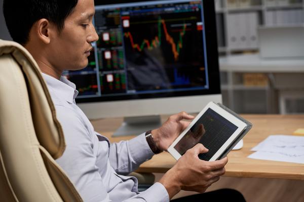 A imagem contém um jovem com uma tela em sua mesa onde aparecem gráficos financeiros. O jovem tem em sua mão um tablet onde aprende mais sobre mercado financeiro para iniciantes.