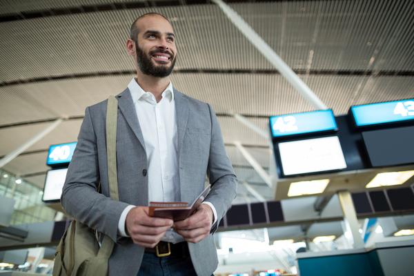A imagem contém um homem sorridente com seu passaporte na mão, olhando para o horizonte, pronto para seguir carreira internacional.