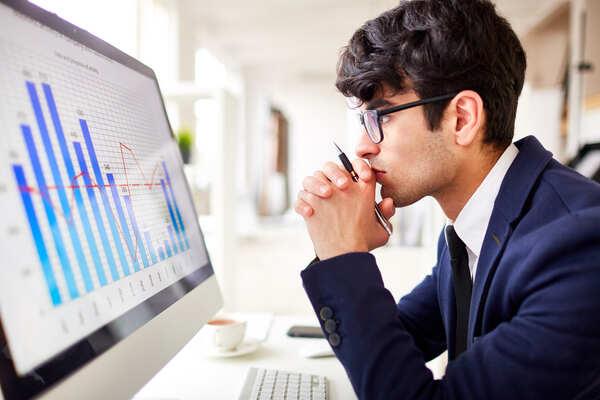 A imagem contém um analista de Ciência de Dados analisando gráficos no computador.