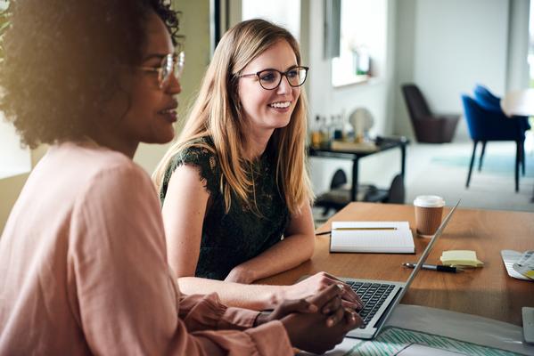A imagem contém duas mulheres sorrindo e conversando sobre o desafio que é fazer gestão de pessoas.