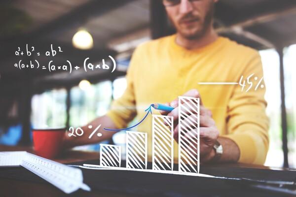 A imagem contém um jovem empreendedor calculando seu orçamento empresarial por meio da análise de gráficos.