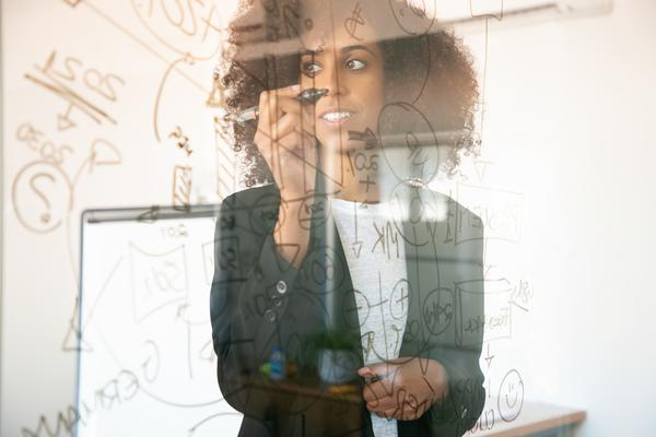 A imagem contém uma jovem empreendedora fazendo contas do seu orçamento empresarial em uma parede de vidro.