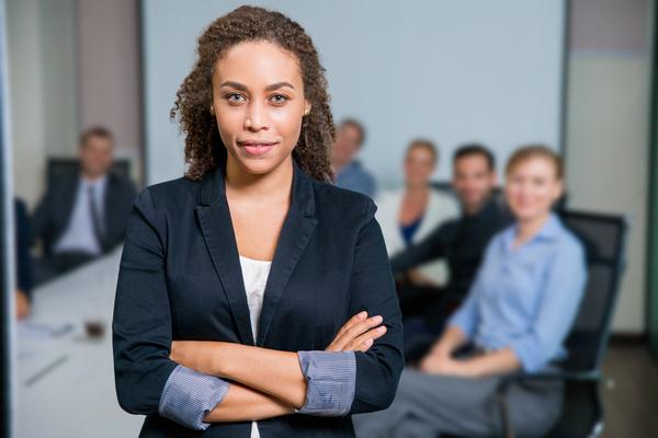 A imagem contém uma empresária à frente de sua equipe promovendo uma excelente gestão de desempenho.