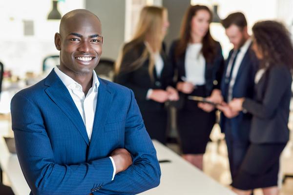 A imagem contém um empresário sorrindo pronto para exercer a inovação na empresa onde trabalha.