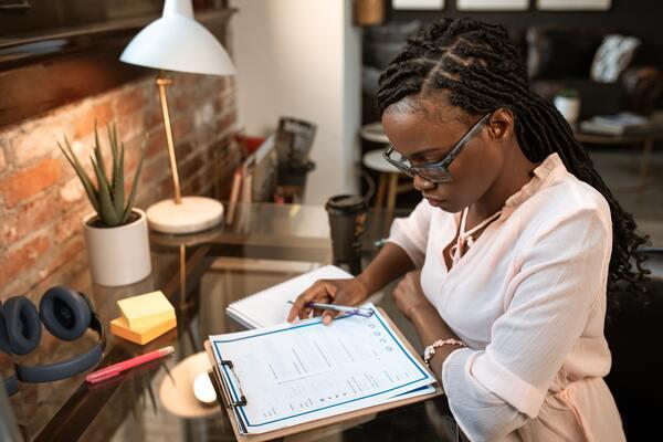 A imagem contém uma jovem estudando para desenvolver inteligência financeira.