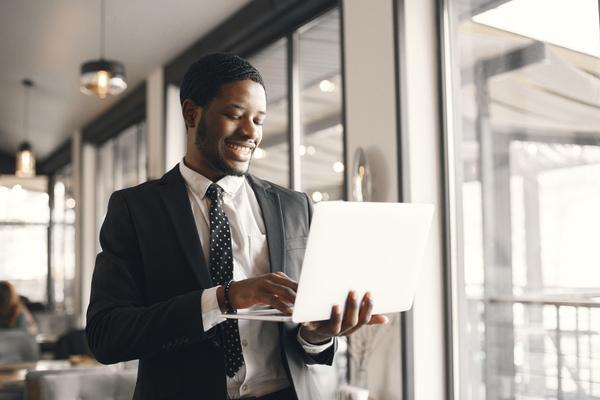 A imagem contém um advogado especialista em Direito Empresarial. Ele está sorridente com seu notebook na mão.